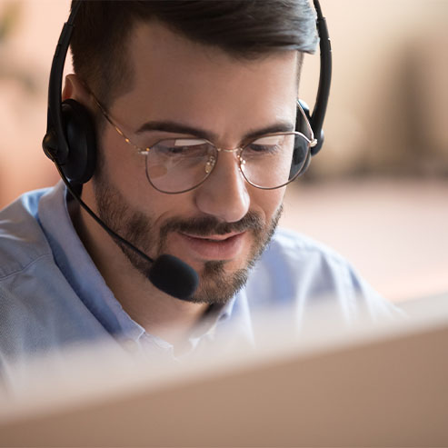 White Man With a Short Beard and Blue Shirt Talking Into a Headset